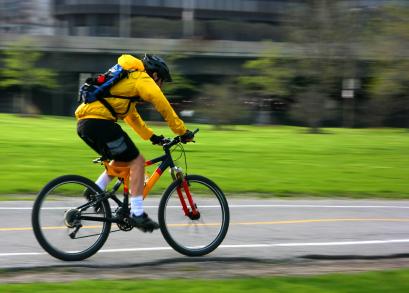 Egy sárga ruhás férfi biciklizik, mögötte homályos épület.
