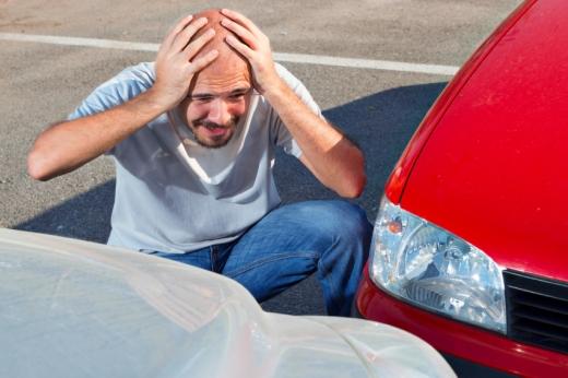 Egy férfi a fejét fogva nézi ahogy nekimentek az autójának.