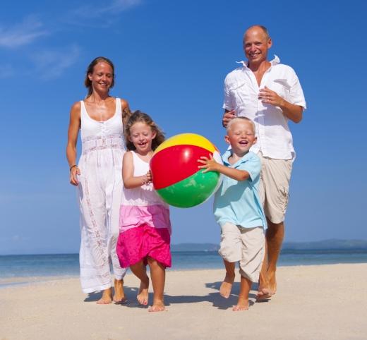 Egy négytagú család a homokos tengerparton áll. a két gyerek kezében felfújható labda.
