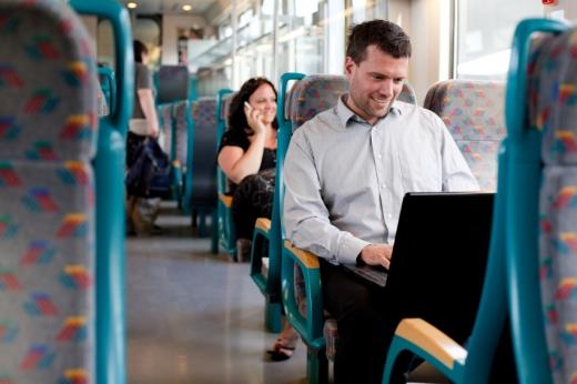 A vonaton férfi laptopot néz, mögötte egy nő telefonál.