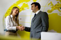 Egy férfi kezet fog egy nővel egy a falon lévő sárgás térkép előtt.