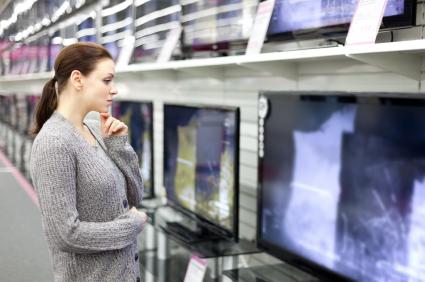 Egy nő gondolkodva nézi egy műszaki áruházban a tévéket.