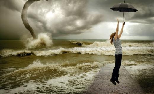 Egy mólón, egy nő nagy viharban kinyitott esernyővel emelkedik fel.