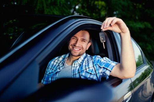 Egy férfi autóba ülve, ránk mosolyogva kitartja a slusszkulcsát.