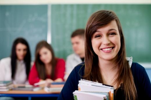 Egy tanuló mosolyog ránk, mögötte három tanuló ül.