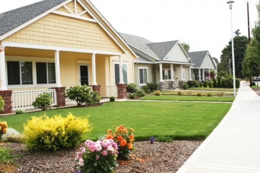 Egy kertvárosi utca, több ház, füves udvarral.