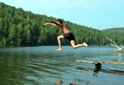 Egy fiú fejest ugrik egy tóba, ami mögött egy erdő van.