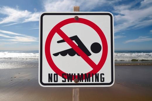 Egy úszni tilos tábla a tenger előtt.