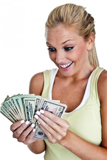 Egy szőke nő nagyon megörül egy csomó papírpénzek ami a kezében van.