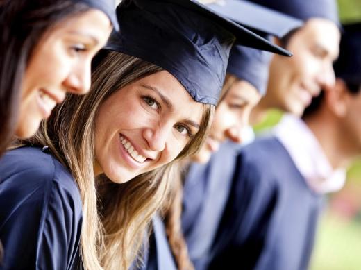 Diplomaosztón lévő fiatalok mosolyognak felénk.