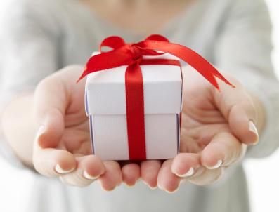 Egy női kéz felénk tart egy fehér ajándékdobozt, piros szalaggal átkötve.