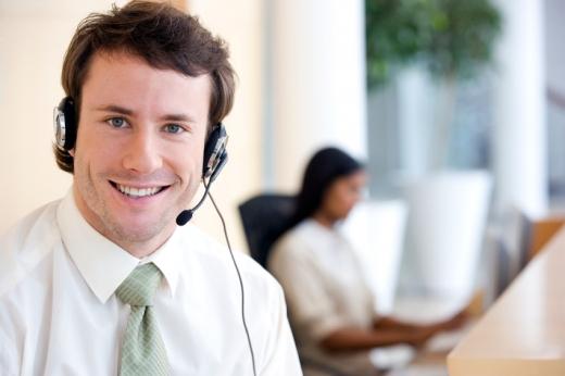Egy mikrofon fejhallgatóval a fején egy férfi mosolyog ránk.
