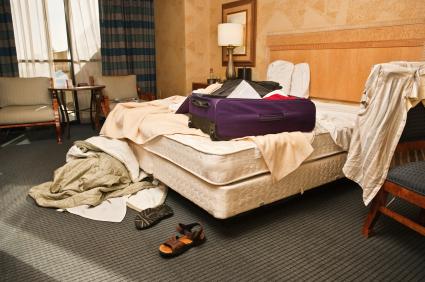 Egy szállodai szoba közepén egy ágy és ruhák mindenfelé.