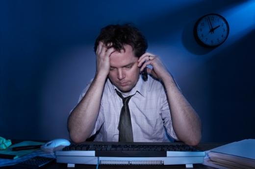 Egy férfi este telefonál és egy számítógép előtt ül.