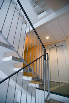 Egy lépcsőház lépcsőjén nézünk a lift felé.
