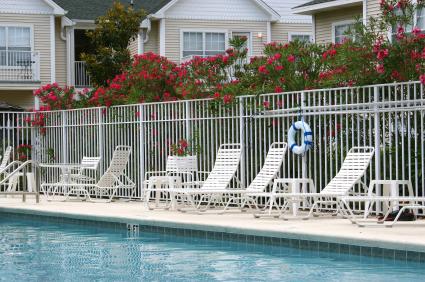 Egy medence mellett fekvő székek és mögöttük apartmanok.