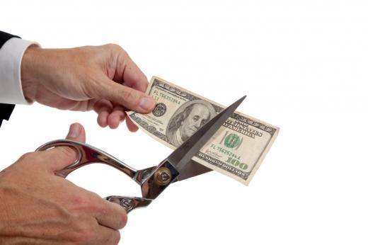 Egy férfi keze papírpénzt tart, a másik keze ollóval elvágja.
