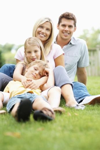 Egy négytagú család egymás mögött a fűben ül.