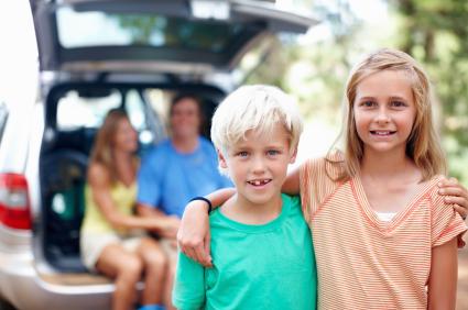Két gyerek néz ránk, hátul a szülők a kocsi csomagterében ülnek.