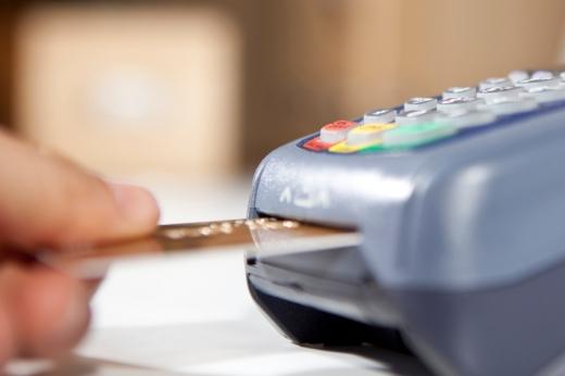Egy kéz éppen bankkártyát dug a terminálba.