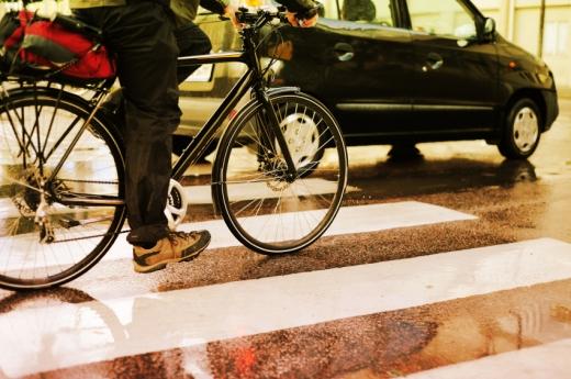 Egy kerékpárás egy autó mellett megy át a zebrán.