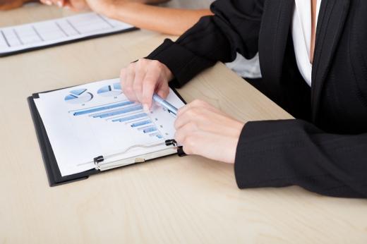 Egy öltönyös férfi kezében toll, előtte az asztalon grafikonok.