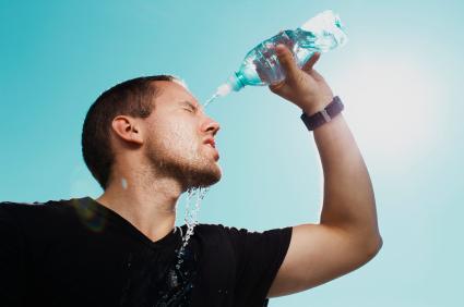Egy férfi fél literes üvegből vizet önt a fejére.