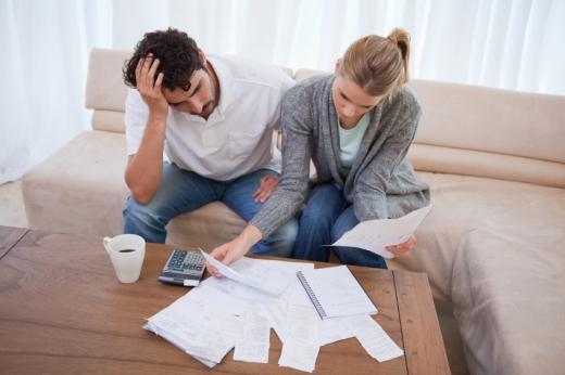 Egy fiatal pár a kanapén ülve papírokat nézeget.