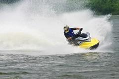Egy férfi jet skivel halad felénk a vízen.