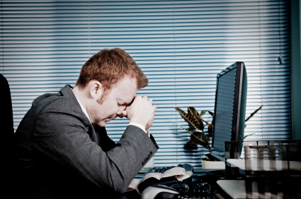 Egy férfi könyökölve, ökle összeszorítva fejét támasztja egy számítógép előtt.