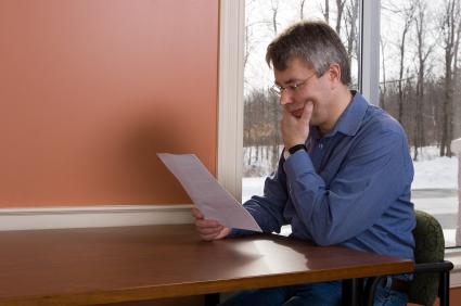 Egy középkorú férfi egy asztalnál gondolkozva szerződést olvas.