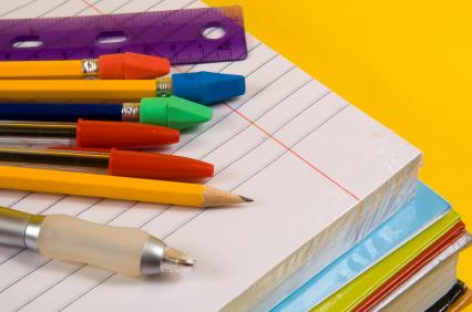 Pár iskolai füzet egymáson és rajta tollak, ceruzák és vonalzó.