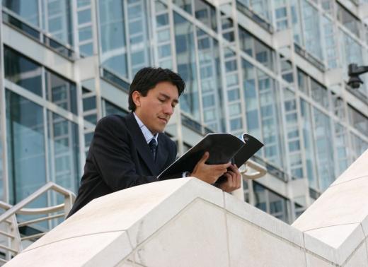 Egy férfi egy kiadványt olvas egy irodaház lépcsőjén.