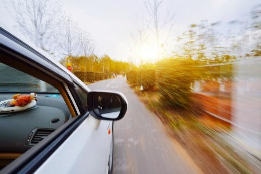 Egy autó gyorsan megy az úton, a környezete homályos.