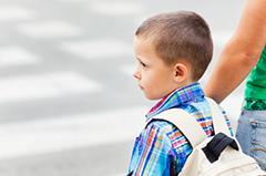 Egy kisfiú iskolatáskával, akit anyukája vezet át a zebrán.