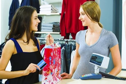 Egy nő ruhát vesz és fizet kártyával a pénztárnál.