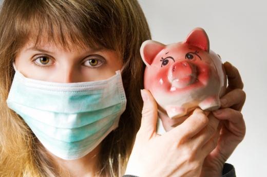 Egy nő szájmaszkkal a száján egy malacperselyt tart a kezében.
