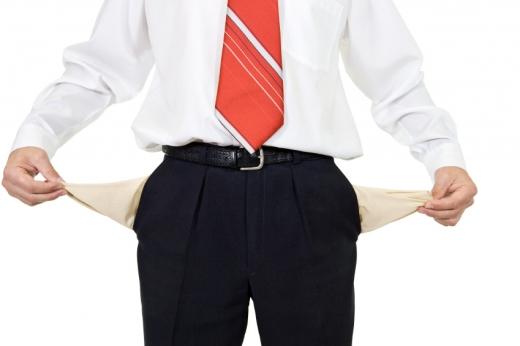Egy öltönyös férfi kifordítja a zsebeit, mutatva hogy üresek.
