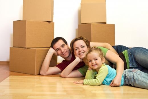 Egy lakásban dobozok között oldalra fekve, könyökölve apa, anya, kislány.