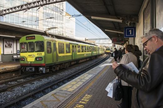 Állomáson utasok várnak a vonatokra, és épp egy zöld vonat érkezik.