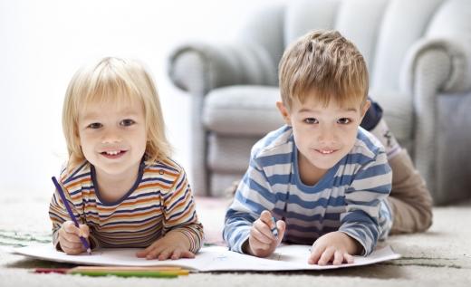 Két kisgyerek hason fekve rajzol és ránk néz.