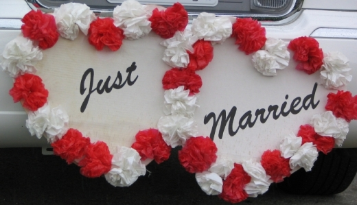 Egy autó hátulján két szív, virágokkal a szélén és JUST MARRIED felirattal.