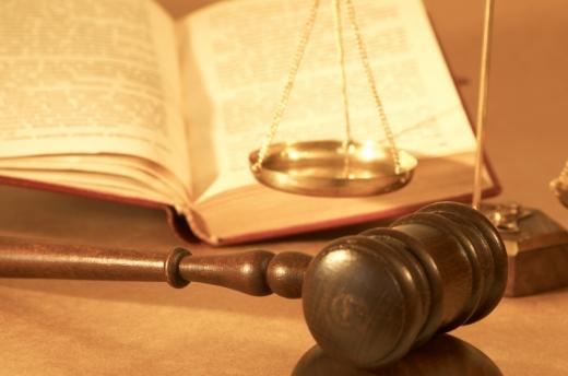 Egy bírói kalapács, jogi mérleg és egy törvénykönyv van az asztalon.