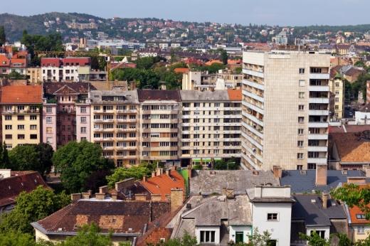 Egy város látképe: elől emeletes házak, hátul családiak.