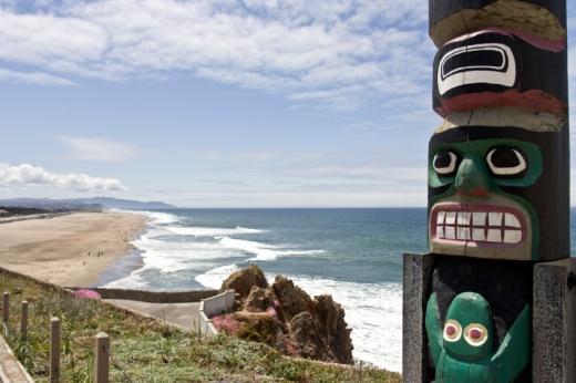 Egy totemoszlop mögött egy tengerpart.