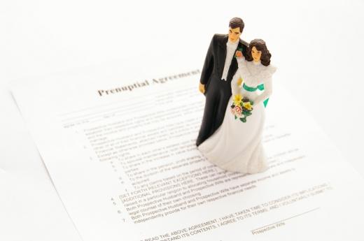 Egy szerződésen menyasszony és vőlegény figura áll.