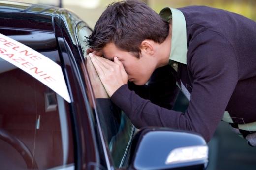 Egy férfi egy eladó autóba néz be a szélvédőre tapadva.