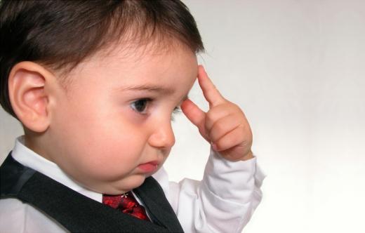 Egy kisfiú az ujját a homlokához emelve gondolkodik.