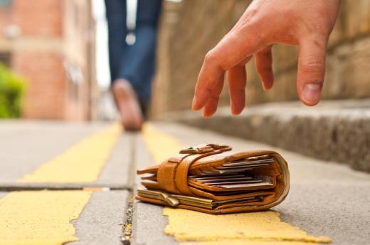 Egy kéz a földről felvesz egy talált pénztárcát.