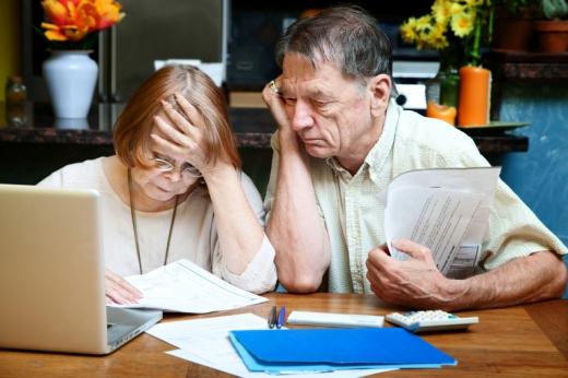 Egy idős házaspár laptop előtt a számláikat nézik gondterhelten.